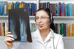 Doctor x-ray foot headset telemedicine. Female doctor or radiologist with headset and an x-ray of a foot in hand as seen through a webcam, telehealth concept Stock Photos