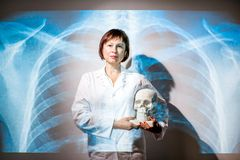 Doctor on the x-ray of human lungs background. Portrait of a senior woman doctor in uniform with projected x-ray of human lungs Stock Photo