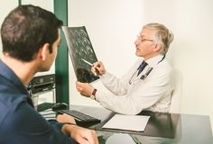 Doctor with x-ray plate. Talking with his patient in a clinic studio - Young men with health problem in hospital receive prognosis from radiologist Stock Image