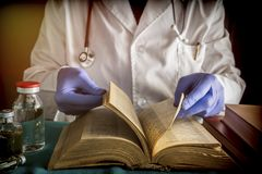 Doctor reading book of old medicine Stock Images
