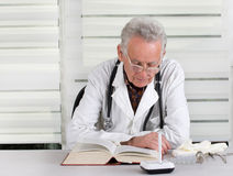 Doctor reading book. Senior doctor with stethoscope around neck reading book in office Royalty Free Stock Photos
