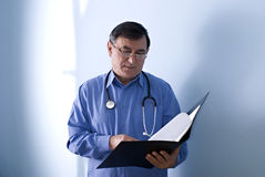 Doctor reading case notes. Half body portrait of middle aged doctor with stethoscope reading medical case notes from folder Royalty Free Stock Image