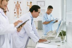 Doctor reading data on computer screen Stock Image