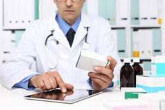 Doctor reading a Digital Tablet with drug boxes in hand Royalty Free Stock Photo