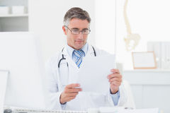 Doctor reading document in clinic Royalty Free Stock Photography