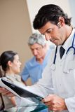 Doctor Reading Document At Reception Royalty Free Stock Images