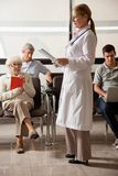 Doctor Reading File With People In Lobby Stock Photo
