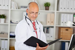 Doctor Reading Folder Against Shelves In Office Royalty Free Stock Photography