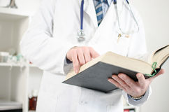 Doctor reading a medical book. In his office Royalty Free Stock Photography