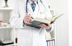 Doctor reading a medical book. In his office Stock Photo