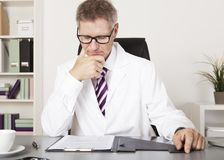 Doctor Reading Medical Results at Office Stock Photography