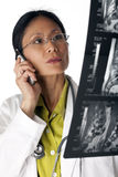 Doctor Reading MRI scan. Asian female doctor looking at an MRI scan while talking on a cellphone. Vertical shot. Isolated on white Royalty Free Stock Photo