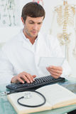 Doctor reading a note at desk in medical office Stock Image