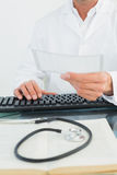 Doctor reading a note at desk in medical office Royalty Free Stock Photography