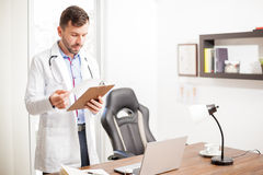 Doctor reading a patient's history in an office Stock Images