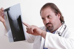 Doctor reading an x-ray. Doctor in a white coat holding an x-ray Royalty Free Stock Photo
