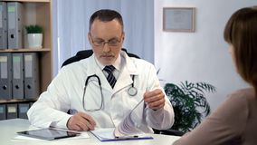 Doctor reading registration form, checking analysis, telling diagnosis to woman stock photography