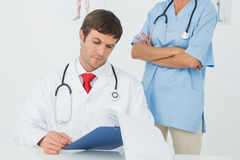 Doctor reading reports beside a nurse in medical office Stock Photos