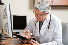 Doctor Reading While Sitting At Desk Stock Images