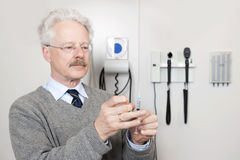 Doctor Ready To Give Vaccination. Mature doctor ready to give vaccination with injection at a clinic Royalty Free Stock Image