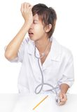 Doctor realizes mistake or malpractice. Young Korean doctor sitting on desk banging his head, realizing a mistake, a malpractice or something he overlooked or royalty free stock photos