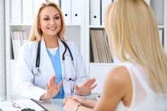 Doctor reassuring her female patient. Medicine, help and health care concept Royalty Free Stock Photography