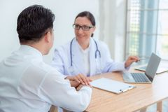 Doctor reassuring her male patient in examination room, Healthcar and medical concept royalty free stock photos