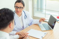 Doctor reassuring her male patient in examination room, Healthcare and medical concept royalty free stock photography