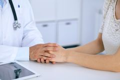Doctor reassuring his female patient by touching her hands while talking. Symbol of support and trust in medicine.  Royalty Free Stock Photos