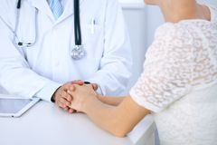 Doctor reassuring his female patient by touching her hands while talking. Symbol of support and trust in medicine.  Royalty Free Stock Photo