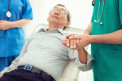 Doctor reassuring his male patient and consulting health problem stock photo