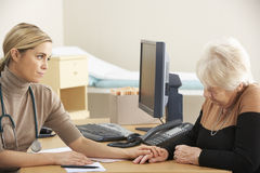 Doctor reassuring senior woman patient Royalty Free Stock Photos