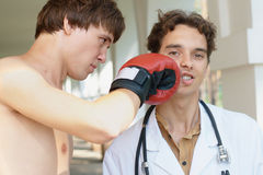 Doctor receiving a punch from angry boxer Stock Photography
