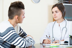 Doctor receiving and questioning teen patient at office Stock Images