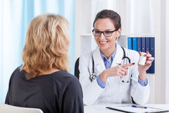 Doctor recommending medicines. For her middle aged patient Stock Image
