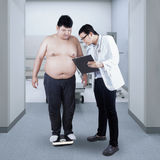 Doctor record the body mass of patient Royalty Free Stock Photos