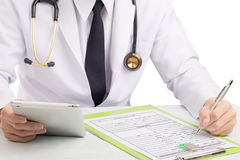 Doctor record history or filling medical form. Stock Photo