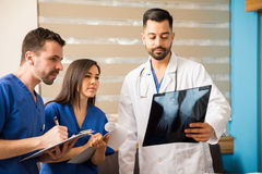 Doctor and residents looking at x-rays Stock Photography