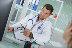 Doctor reviewing condition file Stock Images