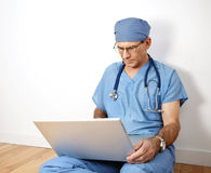 Doctor Reviewing Files on Laptop Royalty Free Stock Photos