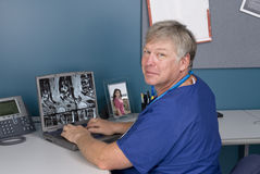 Doctor reviewing MRI on laptop Stock Images