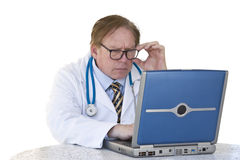Doctor reviewing patient information. A doctor is concentrating very hard and reviewing patient information on his computer Royalty Free Stock Photos