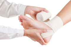 Doctor rewinds a foot bandage to a young man. Isolated white royalty free stock photography