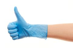 Doctor's hand in blue surgical glove showing thumbs up sign. Close up of female doctor's hand in blue sterilized surgical glove showing thumbs up sign against Royalty Free Stock Images
