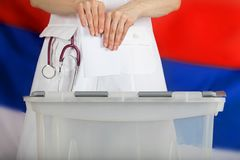 Doctor& x27;s hand casts ballot paper in the ballot box. Russian flag in the background Royalty Free Stock Image