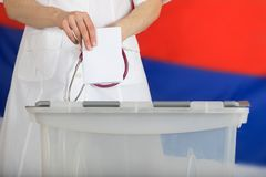 Doctor& x27;s hand casts ballot paper in the ballot box. Russian flag in the background Royalty Free Stock Photos