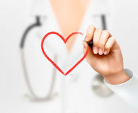 Doctor's hand drawing a heart symbol. Royalty Free Stock Photography