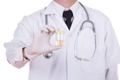 Doctor's hand holding a bottle of urine. Sample Stock Photography
