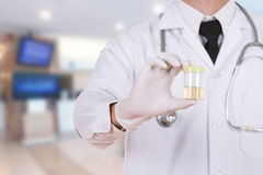 Doctor's hand holding a bottle of urine sample in hospital. Background Royalty Free Stock Photography