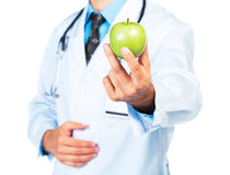 Doctor's hand holding a fresh green apple close-up Royalty Free Stock Images